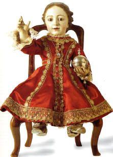 JESUS: sentado y vestido según la usanza cortesana del siglo XVIII.