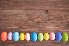 colorful pastel easter eggs on wooden board background with space