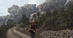 1.fev.2014 - Mulher foge enquanto o Monte Sinabung entra em erupção próximo à vila de Bekerah, no distrito de Karo, na ilha de Sumatra, que fica no oeste da Indonésia. Ao menos 11 pessoas morreram com a erupção do vulcão, que ficou dormente por 400 anos até voltar à atividade em 2010 Imagem: Sutanta Aditya/Reuters