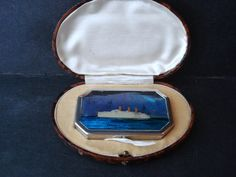 Exquisite POWDER COMPACT EMPRESS OF BRITAIN, Most beautiful unused powder compact, Made in Art Deco style, Sold as a souvenir from ocean liner Empress of Britain, Made in silver tone, lid showing ocean liner famous Empress of Britain, made from what it appears to be butterfly wing and ship was hand painted, sealed under sleek shiny enamel finish,It comes in original box made for this compact, resembling tortoise shell, Never used in mint condition For more antiques and collectibles please…