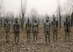 """Models are painted in camouflage colors to blend in with the background as they pose for Chinese artist Liu Bolin's artwork """"Dongji,"""" or Winter Solstice, in Beijing, China on Dec. 20, 2015."""