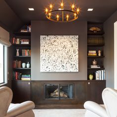 """Rustic Artistry Ebonized white oak cabinets offset the blackened steel fireplace, which is surrounded with wood countertops and """"floating"""" shelves. Design by Nicole Hollis"""