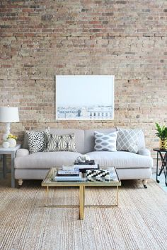 Exposed brick walls and oversized art add a downtown feel to the soft shades of this loft space living room. Love the touches of gold on the modern coffee table, too!