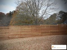 This is a picture of a modern horizontal board wood privacy fence in the fall.