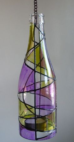 Cut the bottom off a bottle and attach a hanger for a candle. Decorate the outside with glass paint.