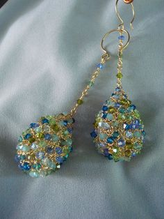 """Crocheted Wire Crystal Teardrop Earrings by dragonswire on Etsy, $76.00  Swarovski 3mm bicone crystals set into a crocheted wire matrix. Hollow form construction with an acrylic bead inserted into the center of the beaded shape to keep them from being squished. Gold filled ear wires and findings . The shape of the earwire keeps the earring from slipping out of your ear lobe.  Total drop 3 1/4 inches Tear drop 1 1/4"""" x 1"""""""