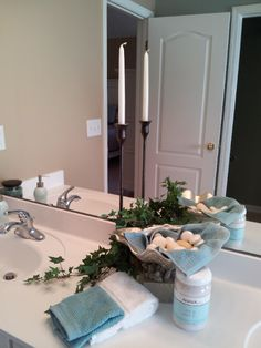 Master Bath staging - keep it simple, clean and consistent.  Here, the use of tall candlesticks, ivy and white towels is repeated on the counter, towel bar and tub.