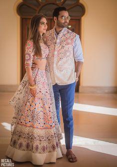 The white lehenga looks beautiful with the bright multicoloured floral prints. The lehenga looks simple yet elegant and apt for any of your wedding ceremonies. Mehendi Outfits, Indian Bridal Outfits, Indian Designer Outfits, Designer Dresses, Indian Bridal Wear, Lehnga Dress, Bridal Lehenga Choli, Lehenga Wedding, Manish Malhotra Bridal