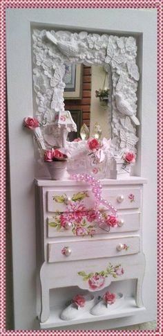Lindo quadro cenário feminino, confeccionado em mdf, pin <br>tura branca, comoda do mesmo material, com decoupage <br>floral e pátina, miniaturas de resina, espelho de resina pro <br>vençal, mini coloarzinho, vasinhos com florzinhas importa <br>das., rico em detalhes! <br>*produto artesanal sujeito a pequenas variações*. <br>Exclusividade Atelier By Dreams!