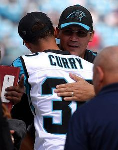 Carolina Panthers head coach Ron Rivera, right, hugs NBA All-Star Stephen Curry, back to camera, prior to the team's game vs the Houston Texans on Sunday, September 20, 2015.