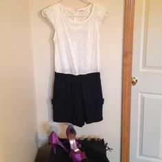 NWT Lace Romper Adorable black an white romper. Top is white lace with cap sleeves, bottom is a black silky material. Shorts have pockets and are fully lined. Comes with a black belt as pictured in photo #4. Brand new with tags, only worn to try on, purchased at a boutique. Size is small and runs true. Item can be modeled upon request. Comes from a smoke free home. ❌NO TRADES❌ Boutique Pants Jumpsuits & Rompers