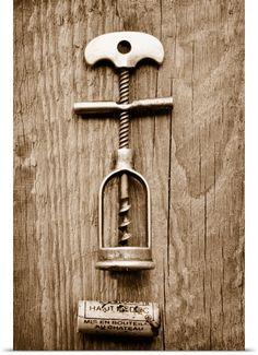 An antique corkscrew and a Haut-Medoc cork on a wooden surface