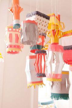 PAPIERLATERNEN KREIEREN Lampions! Falten Sie dafür Papier der Länge nach in zwei Hälften. Über den Falz mit einer Schere Streifen einschneiden, den Papierbogen wieder aufklappen und an der kürzeren Seite zusammenkleben. Die Lampions schmückt man mit farbigen Streifen, Tupfen und Fransen aus Krepppapier. (Bild über: Oh happy day)