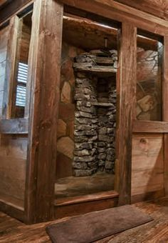 Custom timber frame and rock waterfall shower with interior wall shower windows slate floor and rustic hardwoods in bathroom.