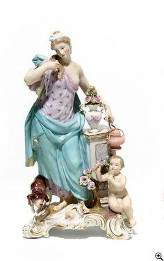Meissen   Allegorie 'Der Geruch'  19.Jh. Modell J.F. Eberlein. Porzellan, farbig und gold staffiert. Aus der Serie 'Die fünf Sinne'. Allegorie in antikem Gewand mit Blumen und Weihrauchgefäß. Begleitet von Putto und Hund. Rocaillesockel mit symbolischer Nase. Höhe 26,5 cm. Schwertermarke, 1051, Bossierernummer 85. Zustand C.