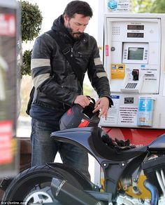 2015 May 11th. Keanu Reeves at a petrol station in Malibu.  50-year-old star can regularly be seen riding around on one of his several motorbikes as he is even a co-founder for the Arch Motorcycle Company.