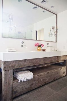 Adore this rustic bench in this bathroom. The dark wood contrasts beautifully with the white, minimalist interiors.