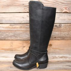 UGG Cierra Black Leather Tall Riding Boots 5.5 NEW NEW! Tall, black and beautiful!  Retail $275 Model # 1008714 Some scuffing from shelf wear. Gorgeous full grain leather upper.  Inside zipper for a secure and flattering fit. Decorative leather straps with bolo tie.  UGGpure sheepsking at ball of foot keeps your feet extra comfy. Molded rubber outsole.  Heel height: 1 3/4 in 100% Authentic UGG Australia product with hologram on back of tag. Photos are of actual item listed. UGG Shoes Winter…