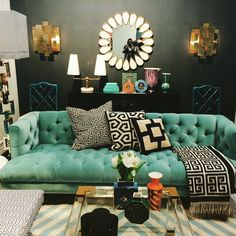A moody room in dark tones brought to life with fun elements, such as the teal sofa and striped rug.