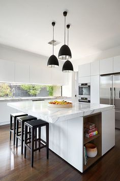 Contemporary White Kitchen With White Marble Countertops, Black Kitchen  Barstools And Several Black Pendant Lights