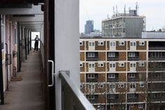 A woman looks out from a residential development in the London borough of Tower Hamlets in London, England. A recent study has shown that 42 per cent of children in Tower Hamlets live in poverty, making it the worst area of the UK for child poverty.