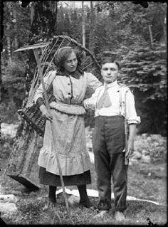 Goglio, Eugenio - Val Brembana. Ritratto di una giovane coppia nel bosco: lei contadina con gerla e rastrello e lui carrettiere con la fune in mano
