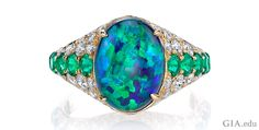 3.50 ct black opal, emerald and diamond ring. Set in 18k yellow gold. Courtesy: Omi Prive