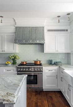 A stainless steel oven range is fixed between white shaker cabinets donning nickel hardware and a gray and white marble countertop fixed against aqua blue glass backsplash tiles, as an ornate French hood is flanked by white upper cabinets. Aqua Kitchen, Shabby Chic Kitchen, Kitchen Backsplash, New Kitchen, Awesome Kitchen, Kitchen Ideas, Kitchen Trends, Backsplash Ideas, Refacing Kitchen Cabinets