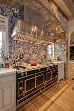 Rustic kitchen with an eye-popping backsplash and beautiful stone arch. By David Johnston Architects via Houzz