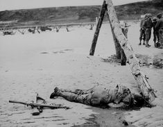 """Crossed rifles in the sand are a comrade's tribute to this American soldier who sprang ashore from a landing barge and died at the barricades of Western Europe."" 1944."
