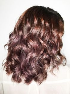 Chocolate mauve is the new hair trend that allows you to go rose gold without dyeing your dark hair blonde. It uses the brown hues in your already dark hair mixed with iridescent pink tones to create a natural, balayage effect.