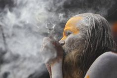 The Shivaratri festival, one of the biggest Hindu festivals dedicated to Lord Shiva. Holy man smokes marijuana; he has smeared his body with ashes.