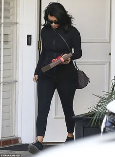A handful:The Kardashian Kollection designer also held onto a brown box with a pink and yellow ribbon, which looked to be chocolates, and a cell phone