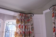 curtains in Jane Churchill Paradise Garden fabric hung from handmade wrought iron poles.