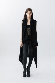 Oversized merino wool vest in pitch black. Braided seams extend into tassels along top and bottom. No ...