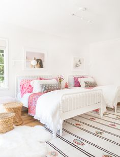 White beds, lighting, rug, pink accents, wicker