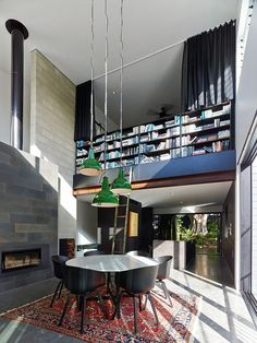 Double height dining room with a wall of books not for the faint of heart [Design: JBS Building & Development]