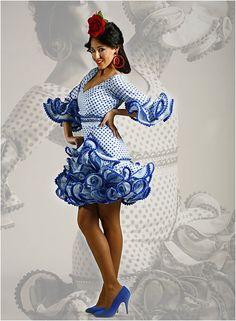 Vestidos de flamenca cortos para Señora de Moda Flamenca 2014, de tres volantes y medias mangas flamencas. Estos tipos de vestidos de flamenca vienen adornados con cintas y madroños, tiene subida lateral, color azulón los lunares y el fondo blanco. http://www.elrocio.es/moda-flamenca-2014-trajes-de-flamenca/1610-vestidos-de-flamenca-temporada-2014.html