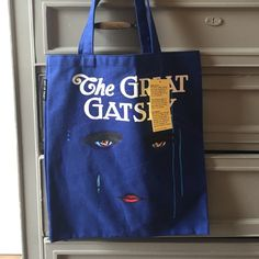 "Great Gatsby tote The iconic cover of F. Scott Fitzgerald's book ""The Great Gatsby"" on a sturdy cotton tote. Features a pocket on the inside. Beautiful blue color, amazing for a true book lover! Out of Print Bags Totes"