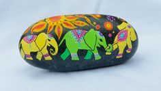 These happy elephants will brighten up your day wherever you choose to display them! They makes an excellent paperweight, rest in potted plants, the edge of your garden, or just sit on a shelf to make you smile when you pass by.  The elephants are painted in acrylic paint and ink on a Maine beach pebble and coated in clear satin finish polyurethane so they will hold up well outdoors too! The stone is approximately 3.5 inches wide by 1.5 inches high and about 3/4 inch thick and can rest…