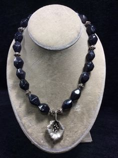 ONE OF A KIND HANDCRAFTED BLUE GOLDSTONE BEADED NECKLACE WITH STERLING SILVER FLOWER PENDANT AND SPACER BEADS. MEASURES UP TO 24 INCHES IN LENGTH.
