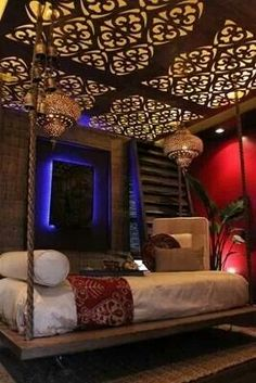 Deep red walls and blue lighting behind the artwork lend a rich quality to this . - Deep red walls and blue lighting behind the artwork lend a rich quality to this relaxing room.