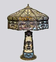 Slag Glass Panel Lamp, it has 8 caramel slag glass panels with 8 blue slag glass panels at the bottom. The whole lamp is covered with filigree. The filigree has birds, cornucopia, roses and urns