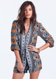 Super cool romper in an allover navy, white, and mustard paisley pattern featuring three-quarter length sleeves and a dramatic V-neckline with hook-eye closures. Finished with a drawstring waist ...