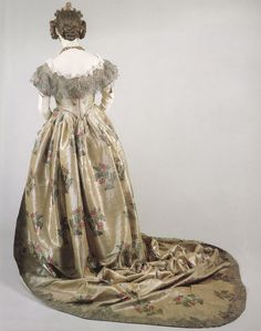 """""""English court dress and train, c. The fabric is silver tissue brocaded in silk floral motifs, with a deep bertha and edging of metalic lace. The costume was worn by Queen Victoria's mother, the Duchess of Kent. Historical Costume, Historical Clothing, 1800s Clothing, Antique Clothing, Victorian Fashion, Vintage Fashion, Vintage Dresses, Vintage Outfits, Court Dresses"""