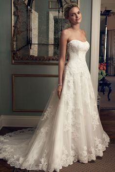 Casablanca Bridal - Covington. Full A-line shaped gown features beautifully beaded lace appliques on tulle and modified sweetheart neckline.Entire bodice has corset boning with sheer lace back panel. Gown is finished with scalloped lace along the hem and matching fabric covered buttons finish the zipper.