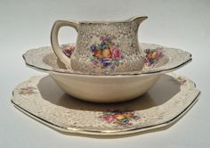 "This pretty plate, jug and vegetable server features a gold all over chintz design adorned with fruit, flowers and leaves. The plate has crimped corners and measures 12"" square. The creamer/ milk pitcher/jug measures 4"" tall x 5"" at widest point and the server diameter is 9 3/4"".  All 3 pieces ar..."
