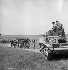German troops surrender to the crew of a British Stuart tank near Frendj in Tunisia, 6 May 1943.