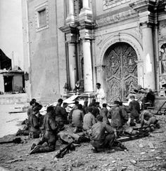 US soldiers kneel during outdoor Mass being conducted by a Filipino priest in front St. Augustin, Manila's oldest Catholic church during a lull in the battle for the city, 25 February 1945