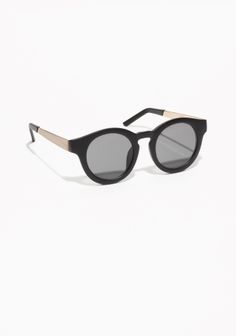 These round sunglasses have robust frames in black and feature sleek gold-tone metal temples.   Read more about our sunglasses  here.